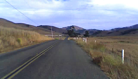 Picture of Chileno Valley Road, black asphalt, grass, and white fence posts disappear into the distance.