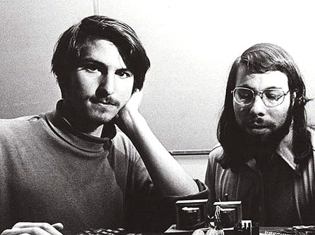 Black and white photo of the two Steves sitting by an original Apple computer
