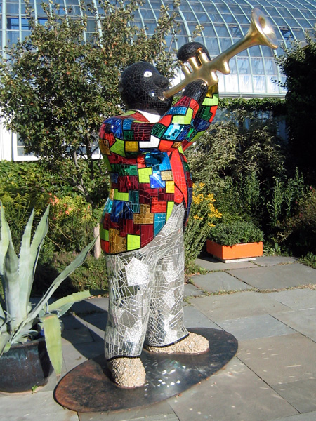 Multi-colored sculpture of Louis Armstrong blowing gold horn