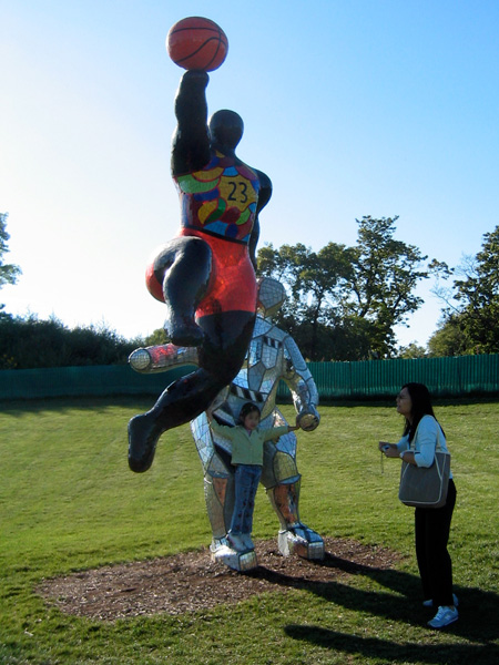 Two figures. Colorful, abstract sculpture of Michael Jordan jumping in air with basketball